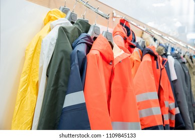 The upper work clothes of strong waterproof fabric of different colors with pockets hang on the hangers as a sample