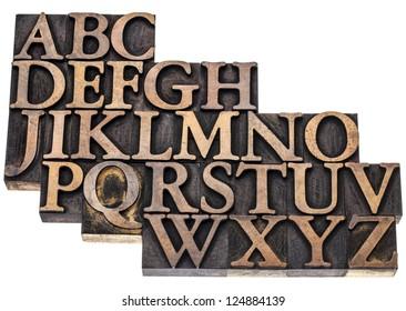 uppercase English alphabet in vintage letterpress wood type printing blocks, isolated on white