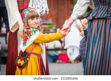 UPPSALA, SWEDEN / JUNE 23 2017: Young girl in Swedish traditional clothes at folk dance during Midsommar festival