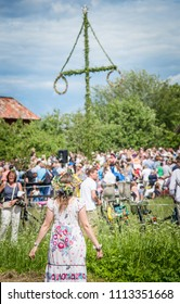 UPPSALA, SWEDEN / JUNE 23 2017: Woman in colorful dress and flower wreath facing maypole during crowded celebration of Swedish Midsommar