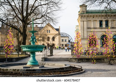 UPPSALA, SWEDEN - Mar 26, 2016 - Street view of inactive fountain with traditional colourful feathers on trees for Easter decorations in Uppsala, Sweden, Europe