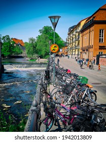 Uppsala Sweden May 17 2019. Bicycle stand in the city center of Uppsala. Small water fall in the river. Old buildings in Scandinavian town. People walking in Swedish city north of Stockholm.