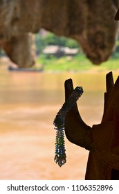 The upraised hand of a buddha is seen in silhouette against a brown river. Crystal hand from his hand. The outline of a cave frame the view. The cave is in Laos.