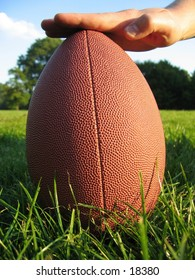 An upright Amarican football in the grass.
