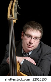 Upright bass virtuoso leaning against his instrument