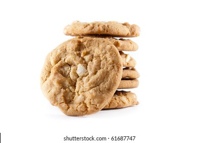 Upright cookies against a stack of macadamia nut cookies on a white isolated background.