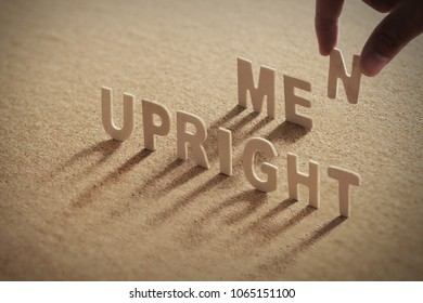 UPRIGHT MEN wood word on compressed or corkboard with human's finger at N letter.