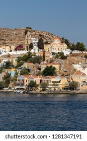 upright photo of the port and village of Symi in Greece