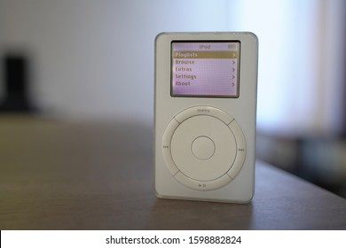 Upright view of a 1st generation iPod sitting on top of a wooden table with the main display turned on. Originally released October 2001. Taken December 26, 2019. San Francisco, CA.