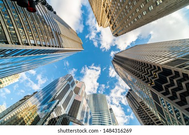 Uprisen angle with fisheye scene of Downtown Chicago skyscraper with reflection of clouds among high buildings which have airplane flying over the sky, Illinois, United States,Business and Perspective