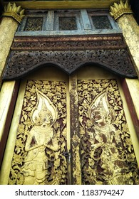 """Uprisen angle image of antique carving Thai pattern or Lai Thai """"Thep Pha Nom"""" decorated on the old wooden door of a building in Thai temple."""