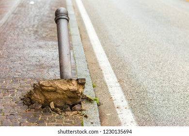 Uprooted and ripped through bollard in city street,