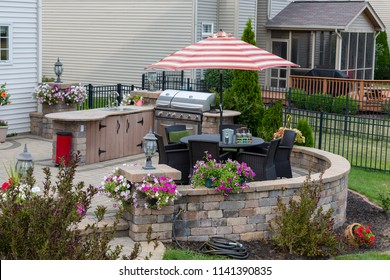 Upscale backyard round brick patio with outdoor kitchen fitted with a gas barbecue and wicker dining furniture under an umbrella