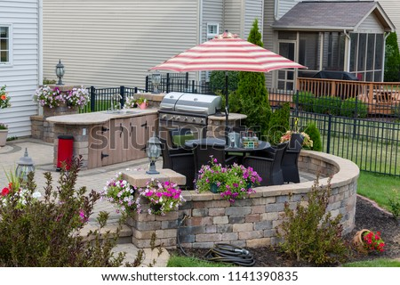 Upscale backyard round brick patio with outdoor kitchen fitted with a gas barbecue and wicker dining & Upscale Backyard Round Brick Patio Outdoor Stock Photo (Edit Now ...
