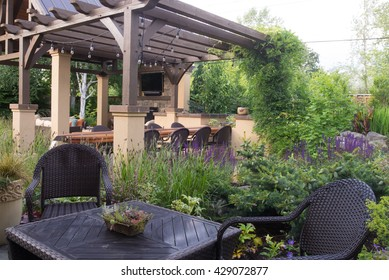 An upscale backyard terrace featuring perennials and with relaxing table and chairs in the foreground.