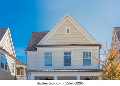 Upscale cottage style homes in suburbs Dallas, Texas with wood siding, covered porch patio with ceiling fans. Colorful autumn leaves and white cladding layer thermal insulation, weather resistance