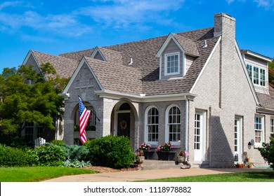 Upscale grey brick home with multiple gables and fireplace and landscaping and flowers and American Flags displayed