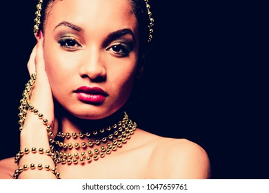 Upscale Indian woman wearing gold jewellery and red lipstick on dark background