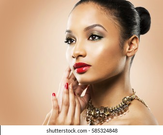 Upscale Indian woman wearing gold jewellery and red lipstick on beige background