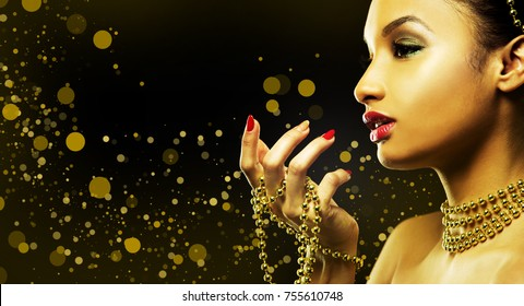 Upscale Indian woman wearing gold jewellery and red lipstick on golden background