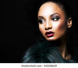 Upscale Indian woman wearing green fur coat and dramatic red lipstick on black background