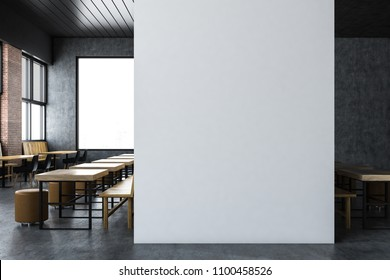 Upscale loft restaurant interior with gray and brick walls, wooden tables and benches standings along them and a mock up wall. 3d rendering