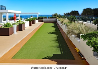Upscale outdoor bocce ball court on an oceanfront terrace, in a condominium, using artificial turf for grass.