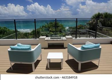 Upscale outdoor terrace with designer furniture overlooking the ocean.
