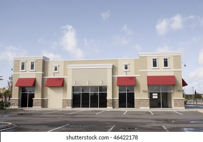 upscale pastel strip mall building with red awnings and tinted glass