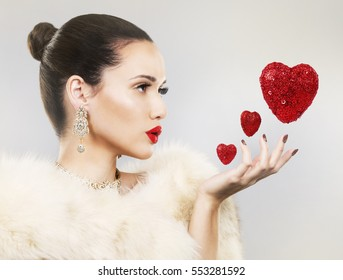 Upscale woman wearing gold jewellery and red lipstick. Red hearts. Light background.