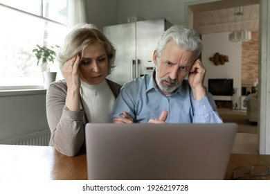 Upset 60s senior couple getting shocking bad news, using laptop together at home, reading email message or talking via video call. Frustrated elder retired husband and wife looking at computer screen