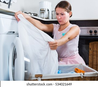 Upset adult woman cannot wash stains off white shirt