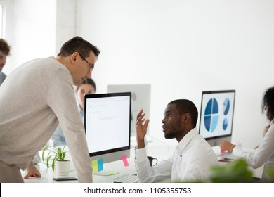 Upset african american employee making excuses, apologizing to serious middle aged boss, begging not to fire him from work, CEO listening to black worker apologies. Close to dismissal concept