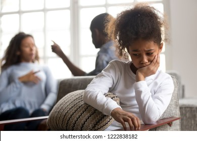 Upset African American girl sitting alone in armchair, parents quarreling on background, preschooler crying daughter suffering from mother and father quarrels, problem in family break up bad relations