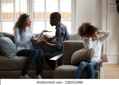 Upset african american kid daughter closing ears not listening to noisy shouting parents fighting arguing at home, sad preschool mixed race child girl stressed with mom and dad black family conflict