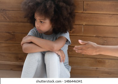Upset african american little adorable kid girl ignoring lent mommys hand. Offended unhappy mixed race child suffering from quarrel, does not want to forgive, feeling stressed and misunderstood.