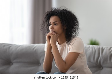 Upset African American woman thinking about problem at home alone, sitting on sofa, looking in distance, health trouble or bad relationships, break up with boyfriend, depression and melancholy