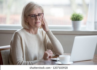 Upset aged woman using laptop at home suffering from headache, tired senior female massaging temples having severe pain or blurry vision, exhausted elderly lady experience dizziness from computer