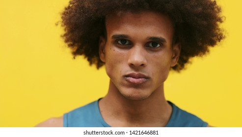 Upset angry young mixed race african american black man with yellow background arms crossed