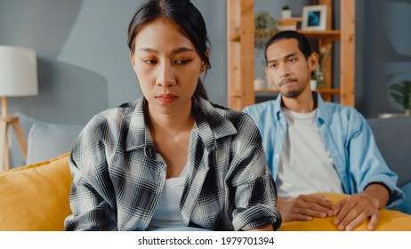 Upset asian couple wife sit on couch listen to furious husband yelling feel unhappy talk negative to her. Couple have fight or disagreement at home, Couple problem, family married toxic relationship.