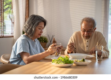 Upset Asian Senior Elderly retired Grandparent stay home with painful face sit on eating table in house. Depressed mature older man and woman couple feeling unhappy, lonely and missing family at home.
