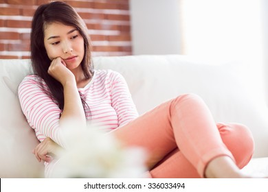 Upset asian woman on couch at home in the living room