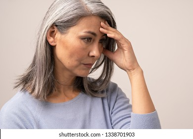 Upset Asian Woman Is Touching Her Forehead. Side View Of Tired Middle-Aged Woman Almost Crying And Covering Her Face With A Hand. Portrait.