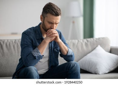 Upset bearded middle-aged man in casual outfit sitting on sofa in living room, thinking about something, looking down, frustrated man having financial problems during pandemic, copy space