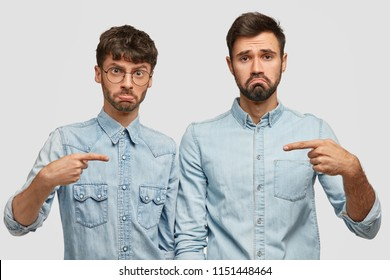 Upset bearded two men frown faces with displeasure, point at each other, have quarrel, argue who should clean car, stand closely in jean stylish outfit, isolated over white studio wall. He is guilty!