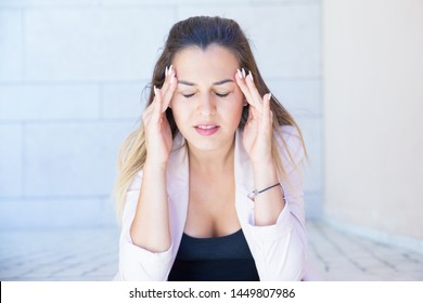Upset beautiful lady suffering from headache. Frustrated young woman with closed eyes touching head and temples with both hands. Head ache and stress concept