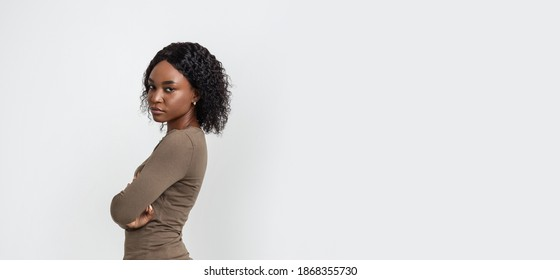 Upset black woman with arms crossed posing on grey studio background, panorama with copy space for text or advertisement. Side view of disappointed african american young lady after fight with lover