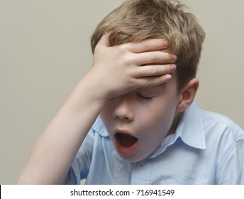 Upset boy puts his hand to his forehead