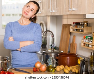 Upset brunette housewife standing at kitchen and trying to cook vegetable soup