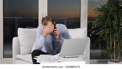 Upset Business Man Receive Bad News while Talk on Phone with a Partner, Multitasking Activity on Office Sofa